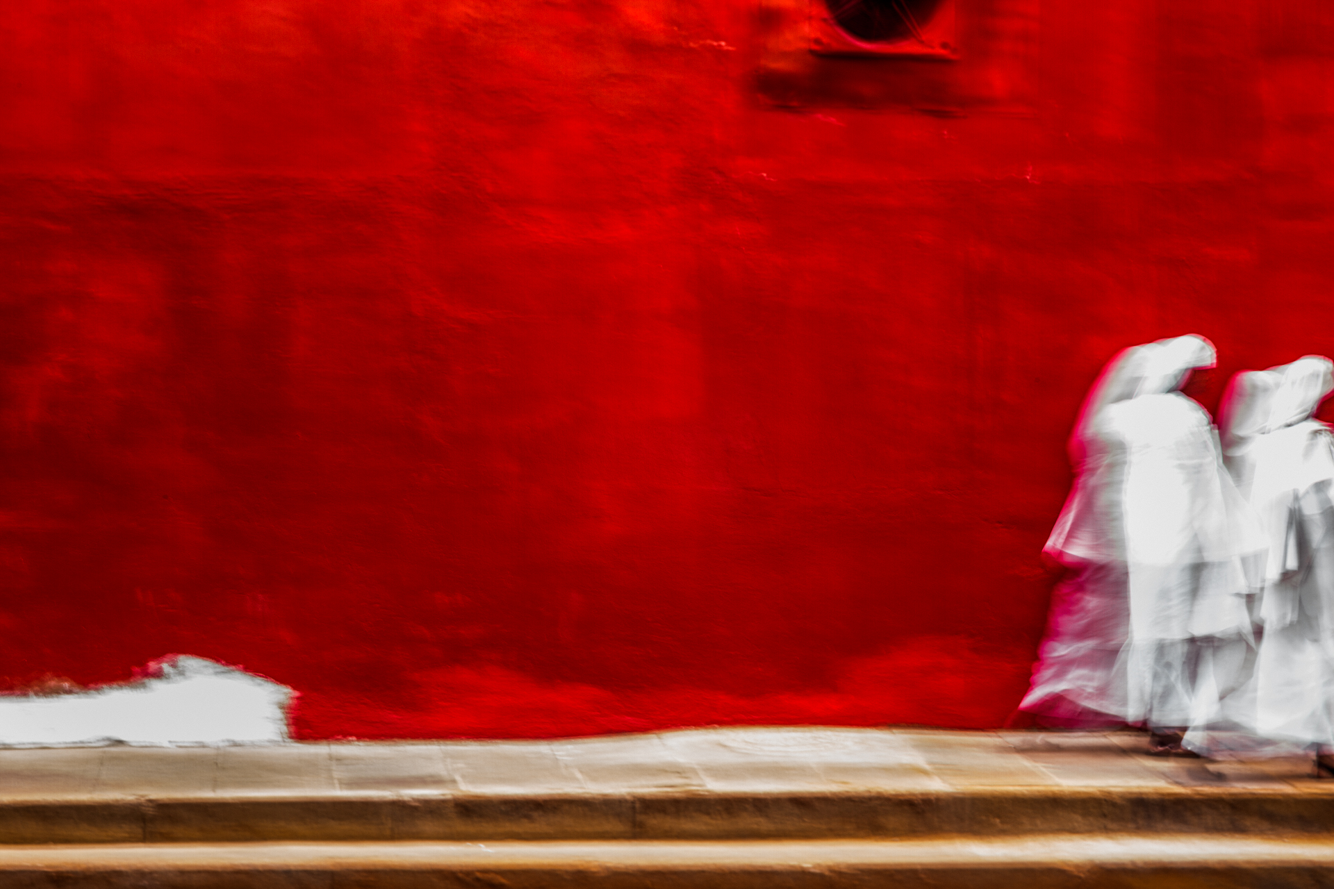 Impressionistic photograph of two women in white cloaks, walking past a red coloured wall in Jeppestown, Johannesburg